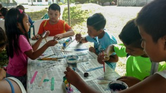 The kids painting lollipop sticks and wax paper.