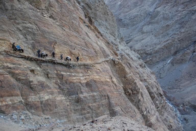 Caravan of hunters and donkeys making its way over a dangerous mountain road in Tajikistan