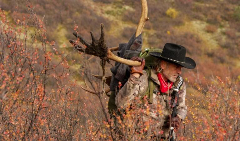 Jim Shockey packing out a caribou