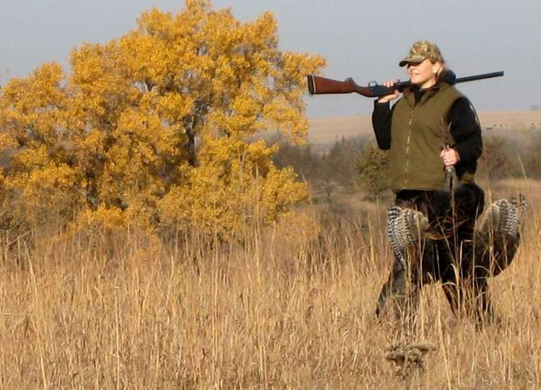 A lady huntress carrying a Merriam's turkey trophy
