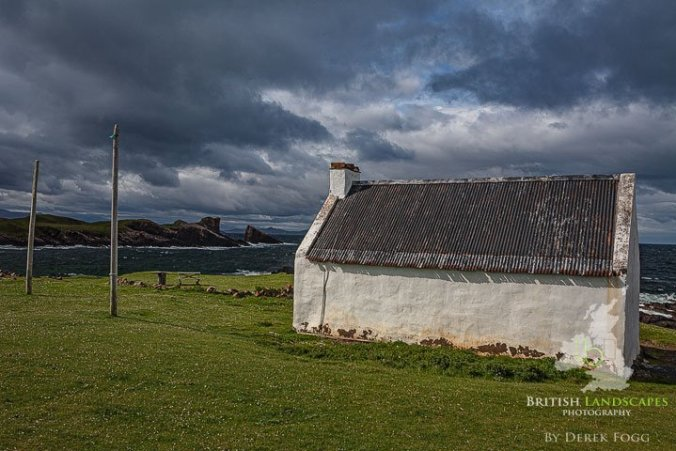 The old salmon bothy and split rock at Clachtoll in Sutherland catches the early evening light under a threatening sky