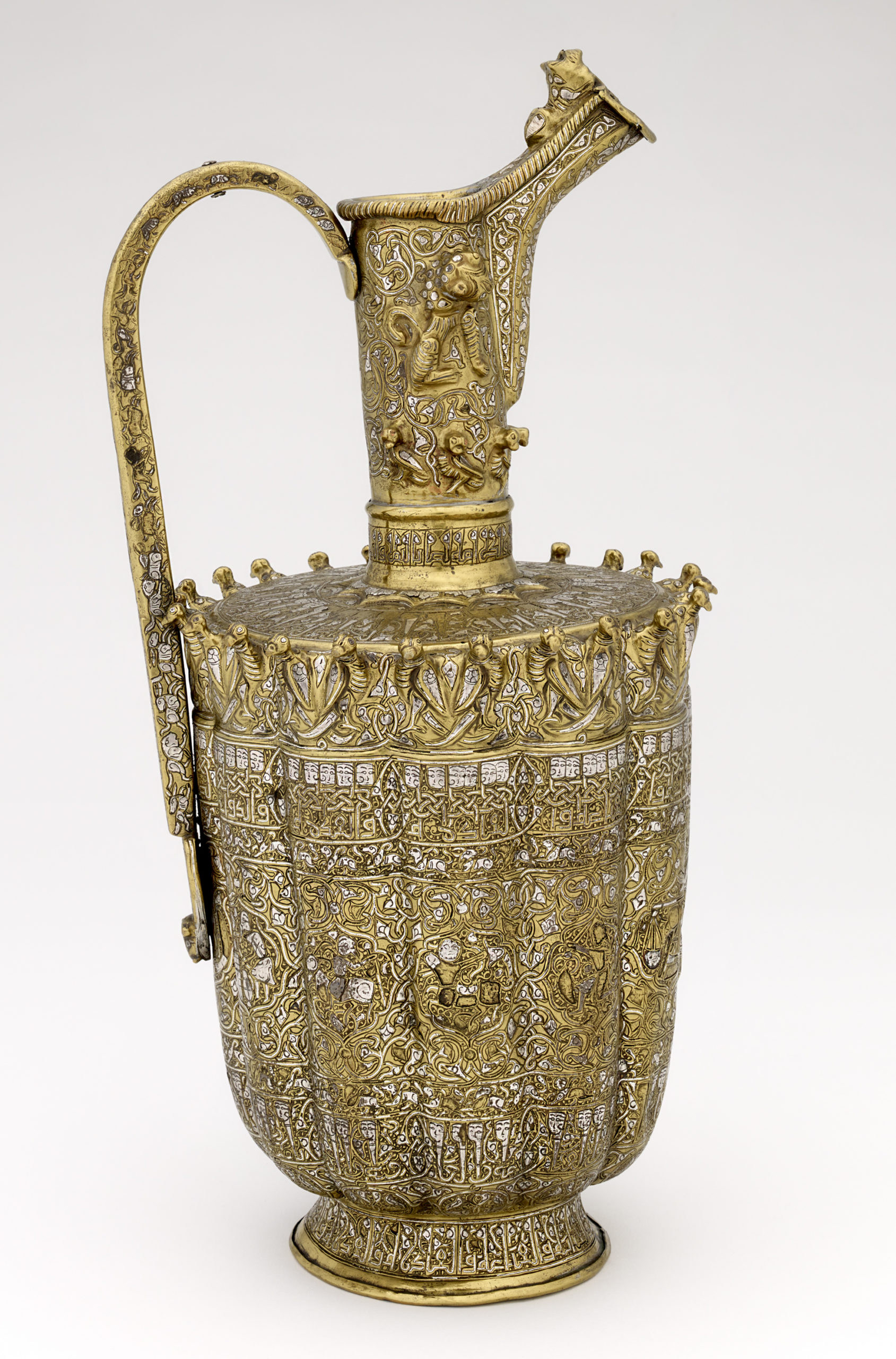 A photograph of a brass ewer, inlaid with silver decoration. The ewer has a large spout which is finely decorated with plant-inspired motifs, the body also features similar decoration. Small birds decorate the rim of the ewer.
