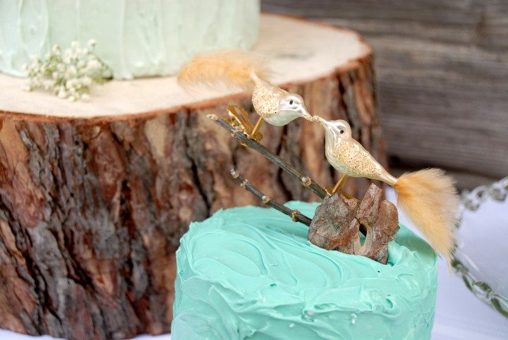 gold love birds clip-on ornament as wedding cake topper at Bronner's on blue groom cake with wedding cake on log slice in background