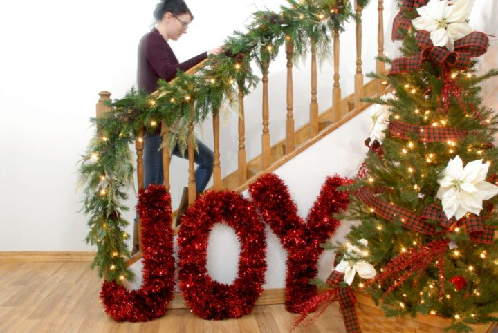 Railing Decorated With Christmas Garland, Christmas Tree, And Giant Tinsel Letters, JOY