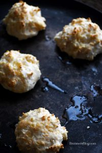 Cheesy Garlic Biscuits with splashes of butter on baking sheet