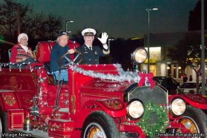 people riding in lighted and decorated antique fire engine in Christmas light parades