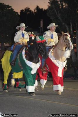 two sheriff's deputies riding costumed horses in Christmas parade