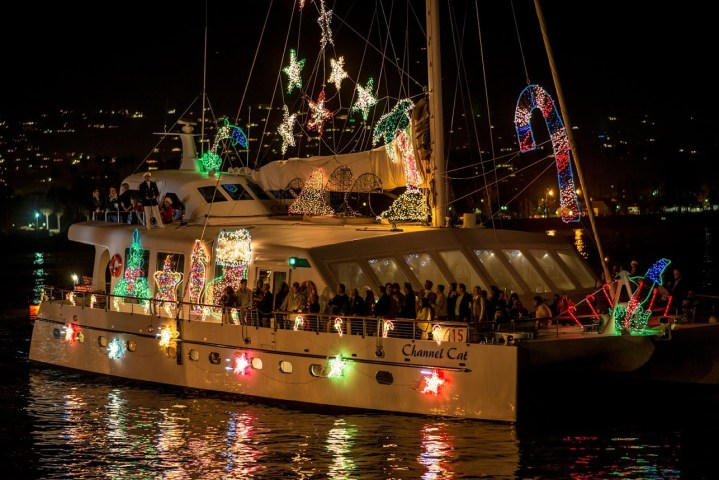 large sailboat loaded with people and decorated with lighted Christmas silhouettes