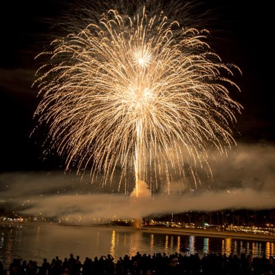 crowd watching fireworks display over the water following Christmas light parades