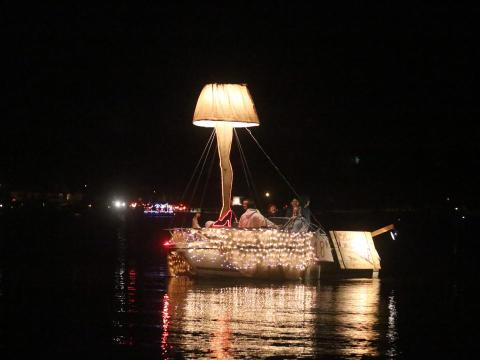 small boat draped in clear lights topped with giant leg lamp for Christmas boat parades in California
