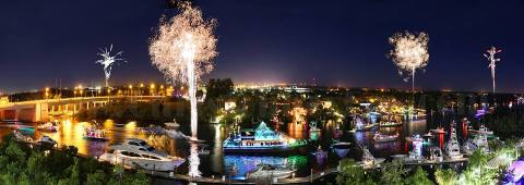 Christmas boat parades in Florida in waterway with fireworks exploding overhead