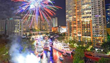 lighted, decorated boats on water surrounded by skyscrapers in Christmas boat parades in Florida