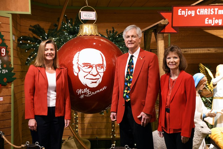 Maria Bronner-Sutorik, Wayne Bronner, and Carla Bronner-Spletzer pose with a life-size memorial ornament of father and Bronner's CHRISTmas Wonderland founder, Wally Bronner.