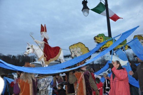people in costume carrying banners and images in Christmas parade