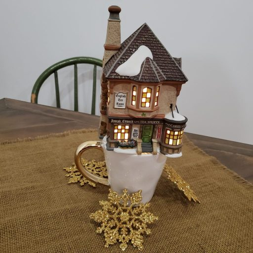 "Department 56 Dickens' Village ""Joseph Edward Tea Shoppe"" displayed atop a white and gold mug on burlap"