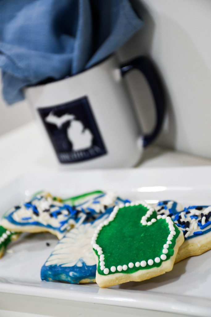 plate of decorated Michigan sugar cookies with Michigan mug stuffed with blue napkin in the background
