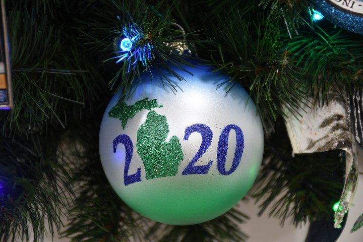 green, blue and white round glass ornament with Michigan's peninsulas and 2020 on it as it hangs from a lighted Christmas tree
