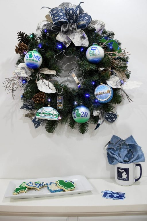 evergreen wreath decorated with blue, green and white Michigan-themed ornaments, a plate of Michigan-shaped cookies, and a Michigan mug and magnet
