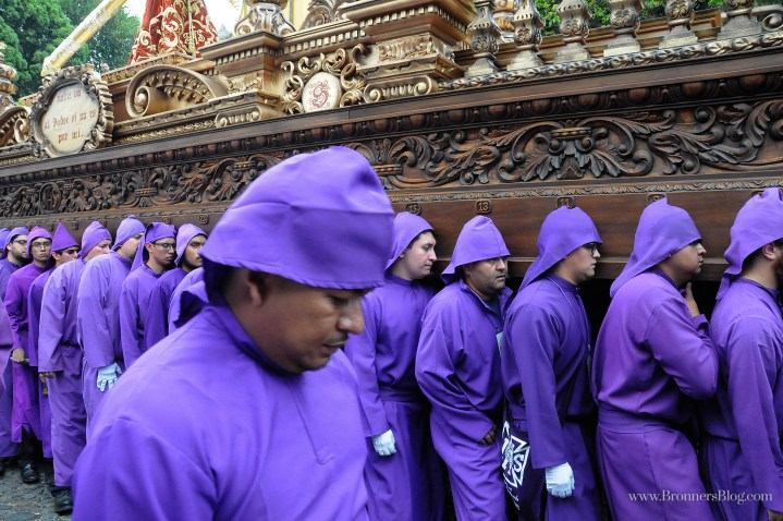 Men dressed in purple robes bear religious a display during a Santa Semana Processional.
