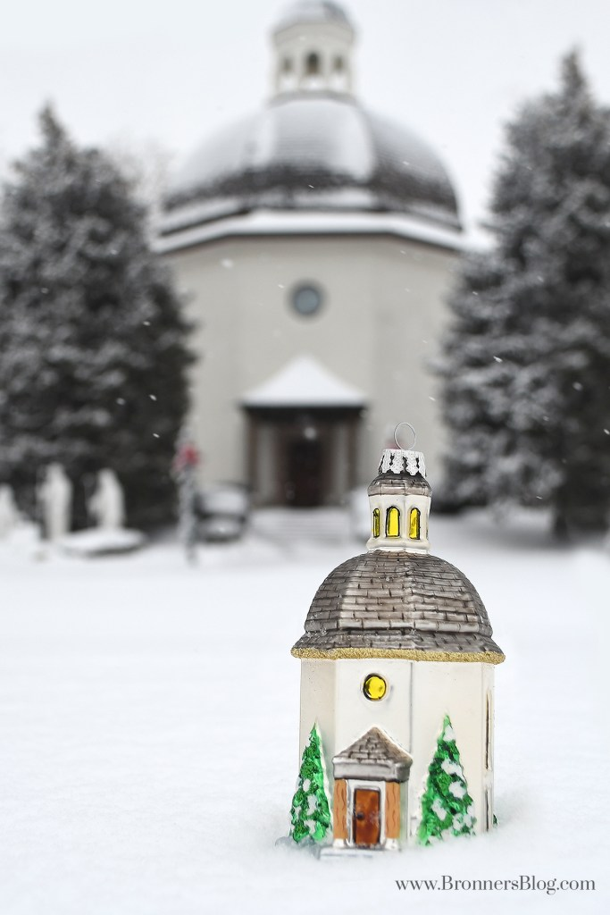 Bronner's exclusive glass Silent Night Chapel ornament sits in the snow in front of the replica chapel located in Frankenmuth, Michigan.