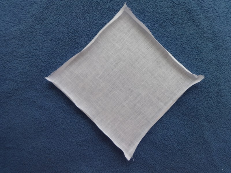 "Napkin with ¼"" folded sides on white linen"