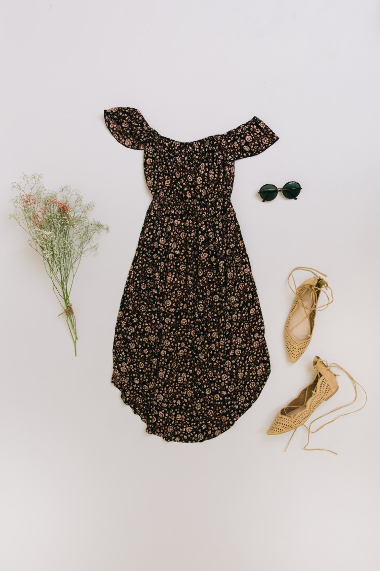 Laydown of a floral off-the-shoulder dress and nude flats.