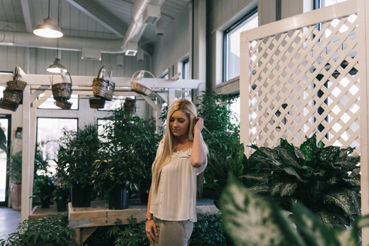Brie standing in shop surrounded by greenery in white, lace-insert shirt paired with grey jeans.