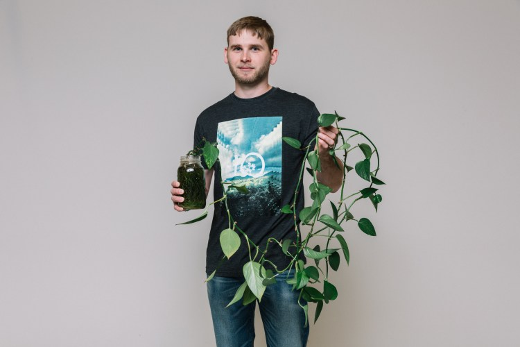 Jake is holding his plant in a glass jar, wearing a tentree t-shirt.