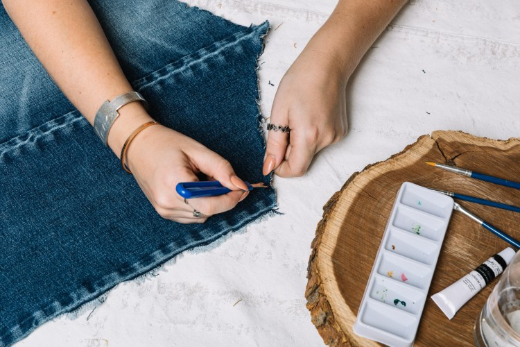 Girl sketching a design to be transferred onto the denim tapestry.