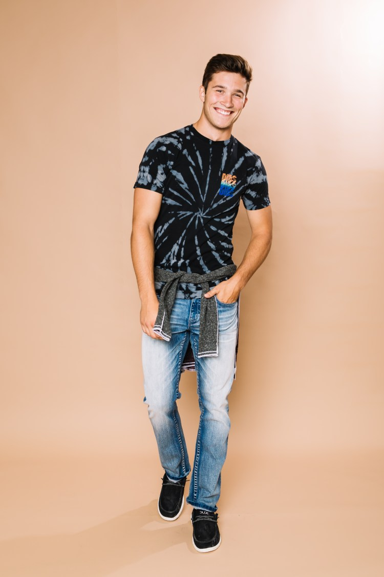Male model wearing Dibs graphic tee with jeans and Hey Dude shoes.