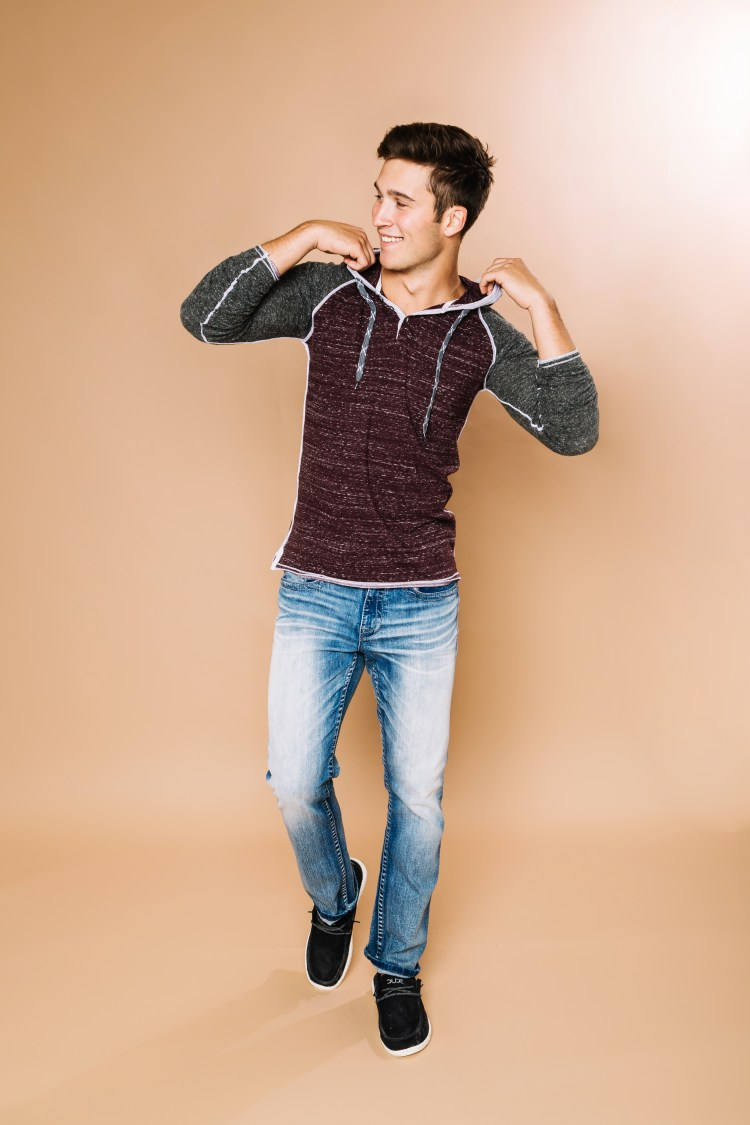 Male model wearing BKE hooded long sleeve shirt with BKE denim and Hey Dude casual shoes.