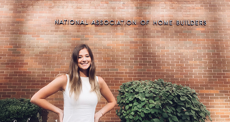 Girl standing in front of a brick wall with hands on her hips