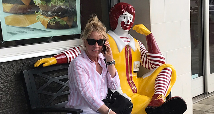 Woman wearing a pink shirt and sunglasses, holding a cell phone to her ear, sitting next to clown statue