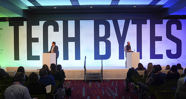 Two men standing on stage with TECH BYTES sign behind them