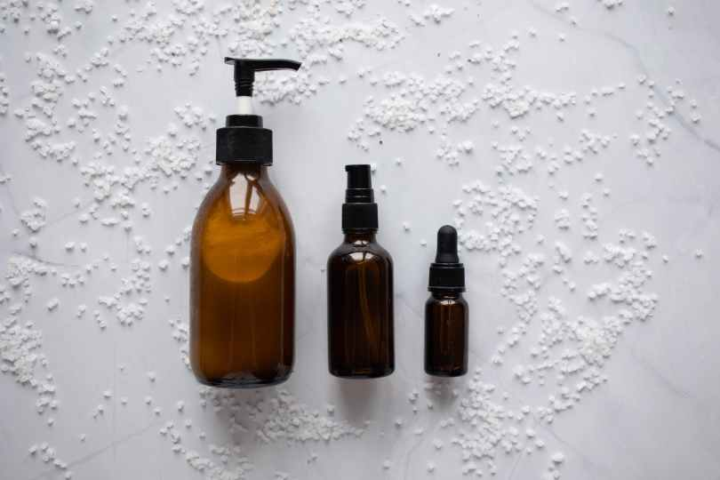 bottles of cosmetic products placed on white surface