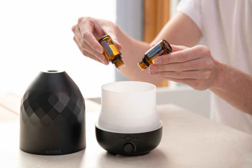 person putting essential oils into a diffuser