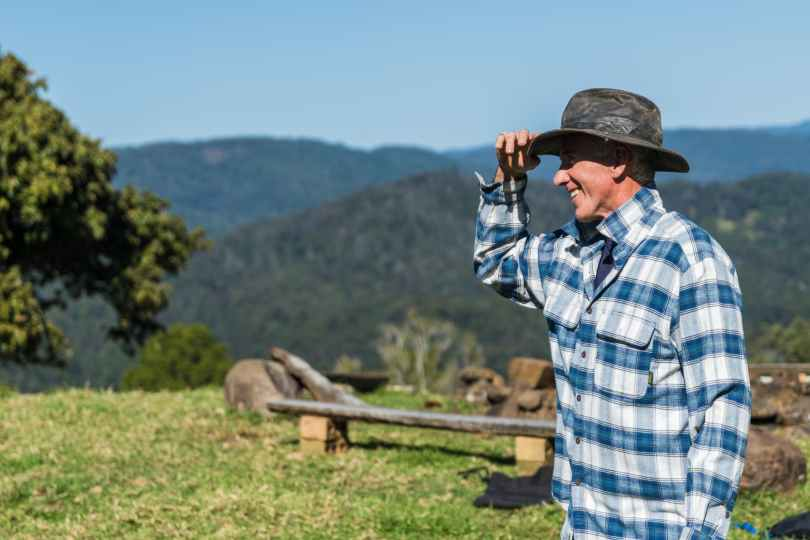 man wearing blue and white checked sport shirt and black hat