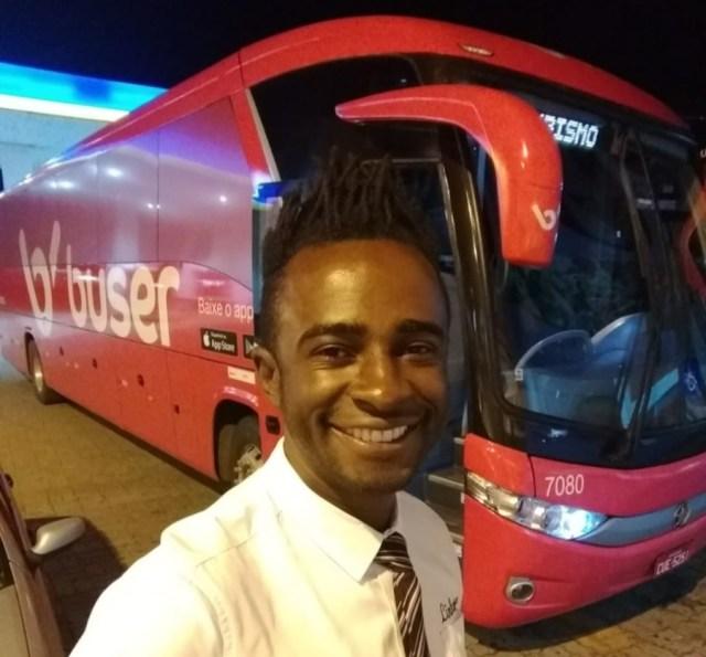 Genilson posando uniformizado em frente ao ônibus para o Dia do Motorista