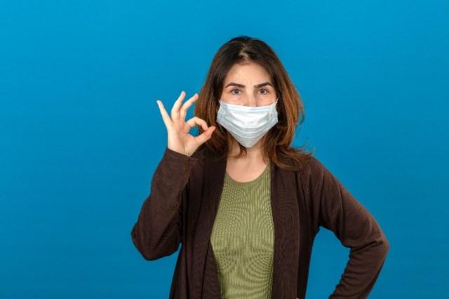 na imagem uma mulher branca usa uma máscara cirúrgica contra o coronavírus, indicando o jeito certo de usar a máscara em viagens.