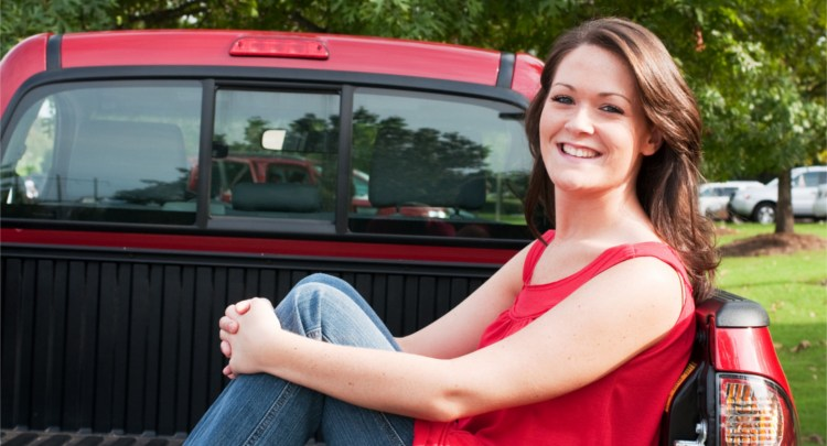 women in a red shirt enjoying the new bedliner in her truck bed