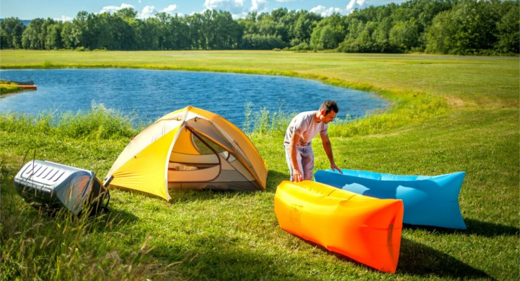 man inflating two inflatable loungers while camping by a lake