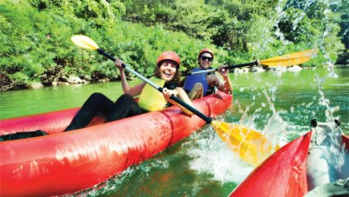 Friends Laughing and Splashing In Red Inflatable Kayaks