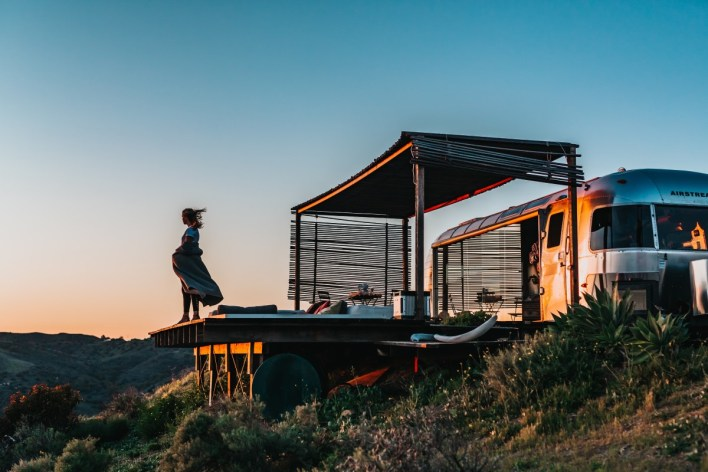 a woman stands on the deck of her camper trailer overlooking a mountain sunrise