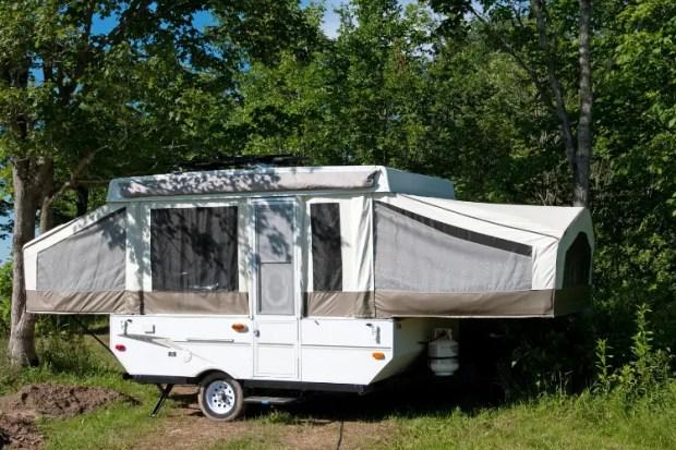a pop up camper trailer setup in the woods