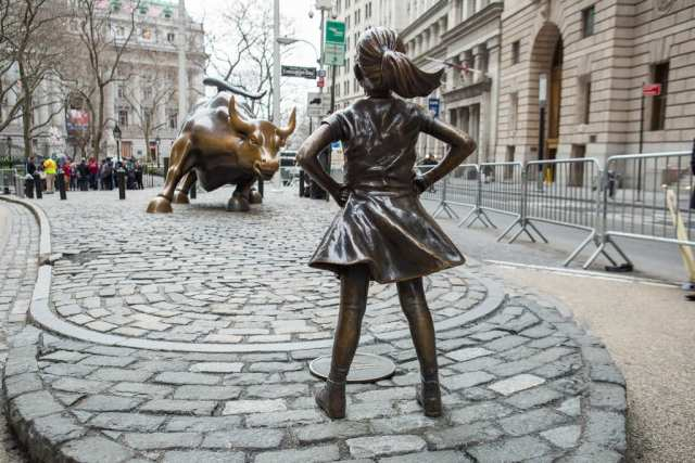 The Fearless Girl bronze statue facing the Charging Bull statue on Wall Street