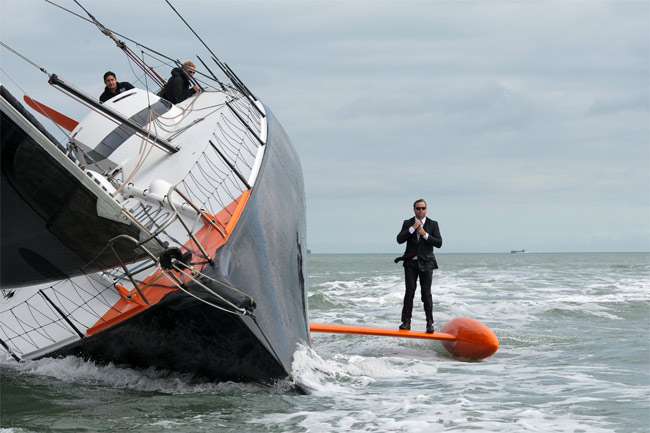 Alex Thompson standing on the keel of the Hugo Boss yacht