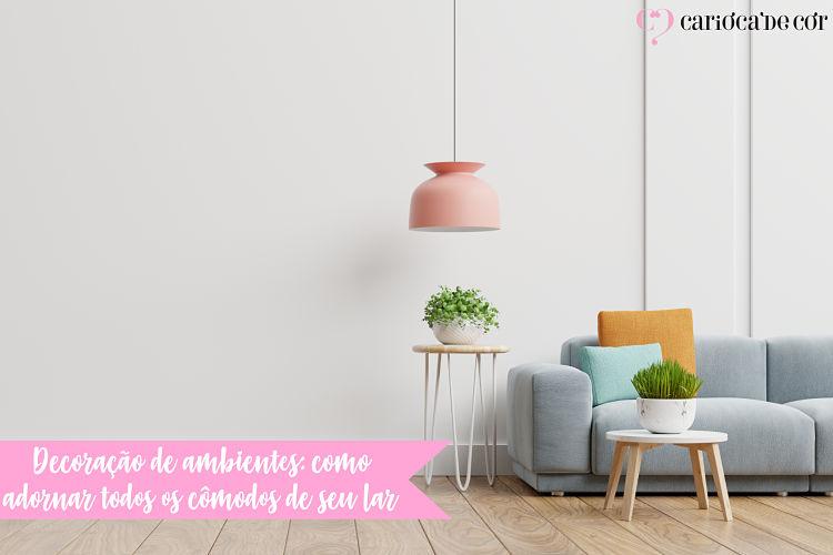 Sala de estar com sofá cinza e decoração com plantas e lustre rosa
