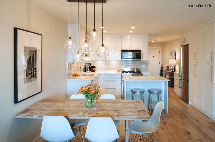 Espaço divido com cozinha e sala de jantar, com decoração em branco