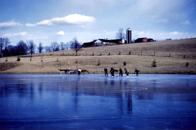 Skating on the big pond. The farm on the hill belonged at the time to the Farnam family