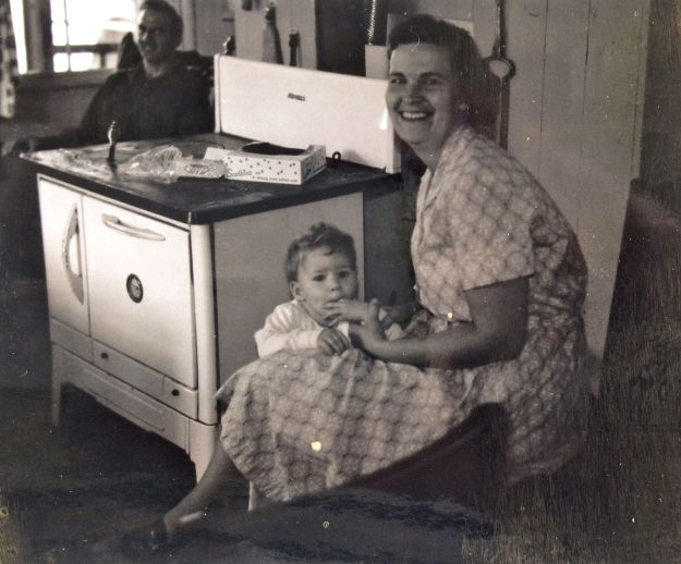 Patti Hall Burkett with her parents, Aaron Hall (in rocker), and Barbara Hall (with Patti) near the newer wood stove -- Photo courtesy Patti Hall Burkett
